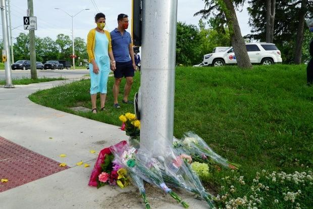 A couple pays respects at a makeshift memorial in London, Ont., on Monday, where four family members were killed Sunday in a hit and run that police believe was planned.  (Colin Butler/CBC - image credit)