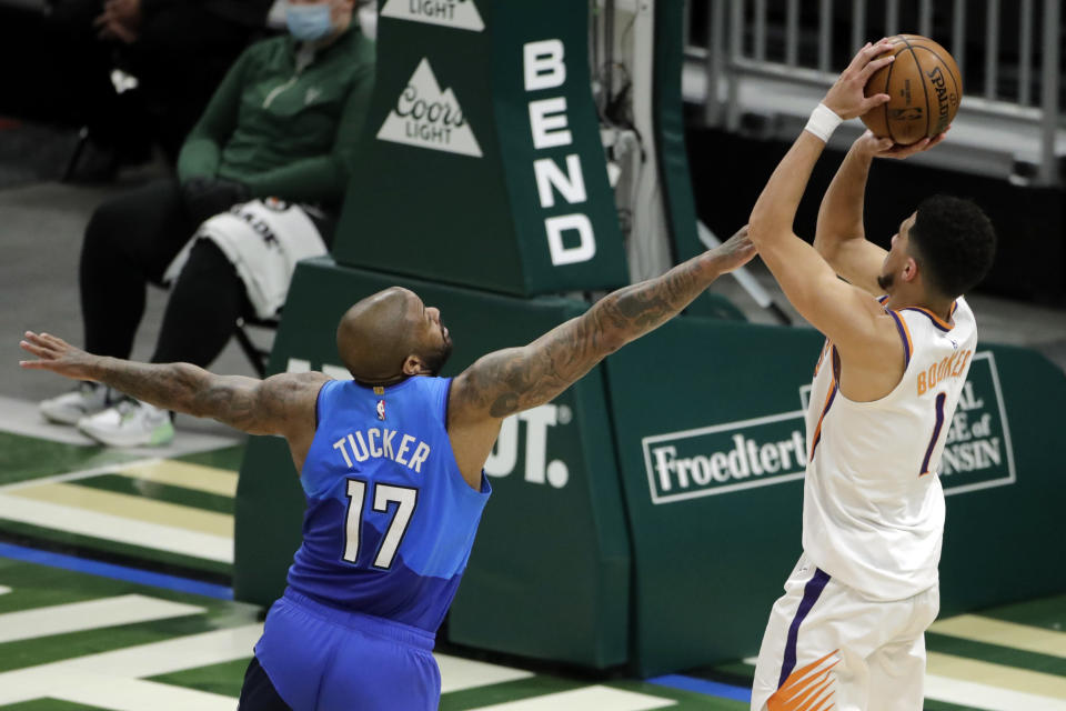 Milwaukee Bucks' P.J. Tucker (17) defends Phoenix Suns' Devin Booker (1) as he shoots during the first half of an NBA basketball game Monday, April 19, 2021, in Milwaukee. (AP Photo/Aaron Gash)