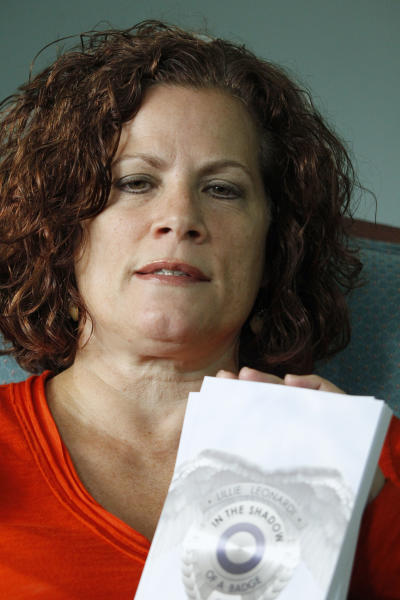 "Lillie Leonardi sits in her living room and shows some copies of her book ""In the Shadow of a Badge: A Spiritual Memoir,"" on Tuesday, July 3, 2012, in Arnold, Pa. Leonardi, a former police officer who retired from the FBI due to post-traumatic stress disorder from her time as a liaison between law enforcement and the victims of United Airlines Flight 93 has written a book about seeing legions of angels guarding the site where the hijacked airliner crashed on Sept. 11, 2001. (AP Photo/Keith Srakocic)"