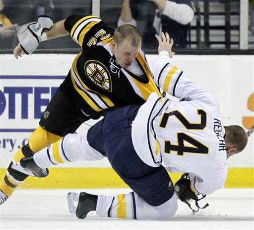Boston Bruins' Shawn Thornton (22) and Buffalo Sabres' Robyn Regehr (24) fight in the first period of an NHL hockey game in Boston, April 7, 2012. (AP Photo/Michael Dwyer)