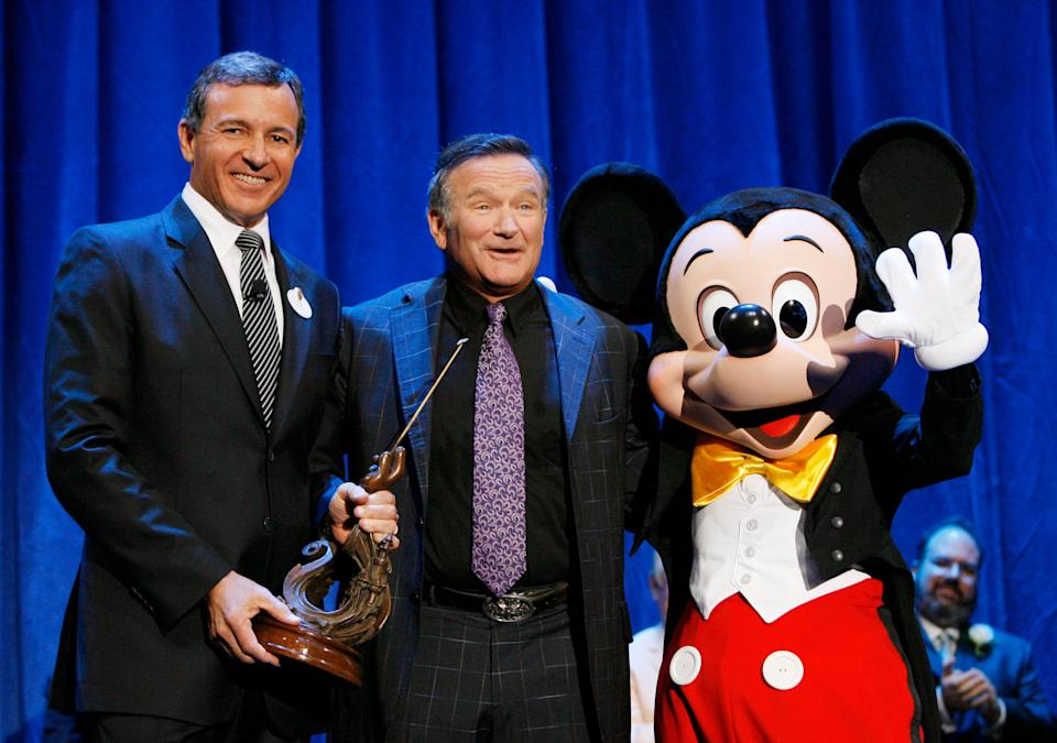 """ANAHEIM, CA - SEPTEMBER 10:  In this handout image provided by Disney, actor Robin Williams (C) is recognized by Bob Iger, CEO of Walt Disney Co.,and Mickey Mouse for Williams' work in """"Aladdin,"""" """"Good Morning, Vietnam"""" and """"Dead Poets Society"""" in a presentation announcing the D23 Expo September 10, 2009 in Anaheim, California. This fall, Williams stars with John Travolta in Walt Disney Films' """"Old Dogs.""""  (Photo by Adam Larkey/Disney-ABC Televsion Group via Getty Images)"""