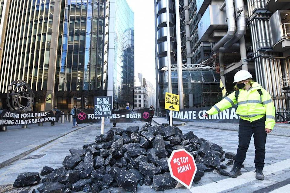 <p>An activist points to a mound of fake coal outside insurance market in central London</p> (Gareth Morris)