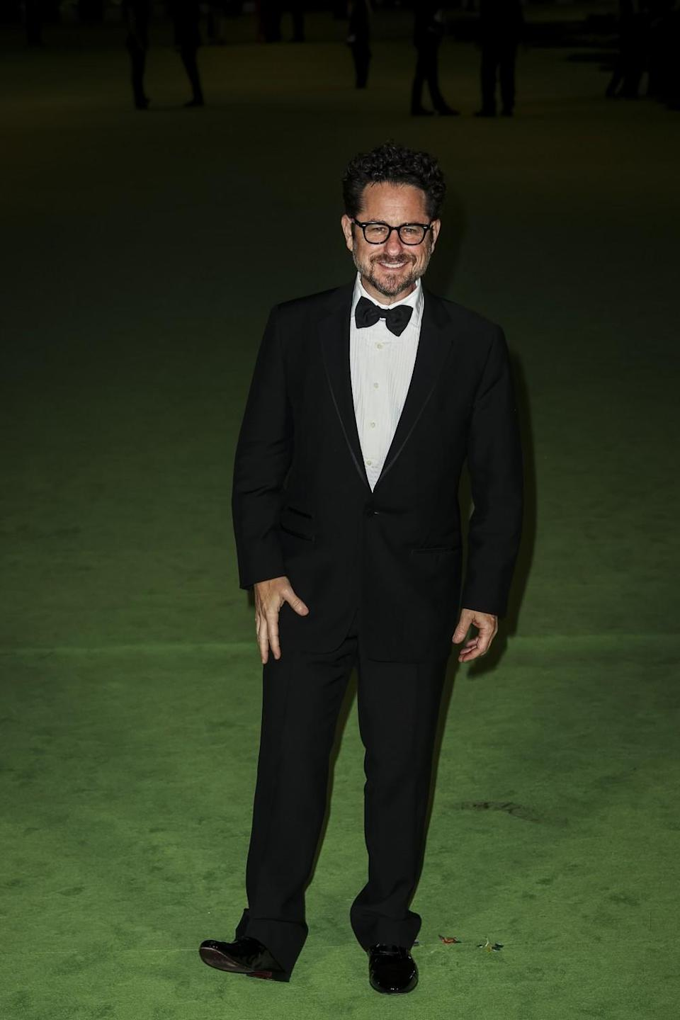 A man in a black tuxedo and bow tie posing on a green carpet