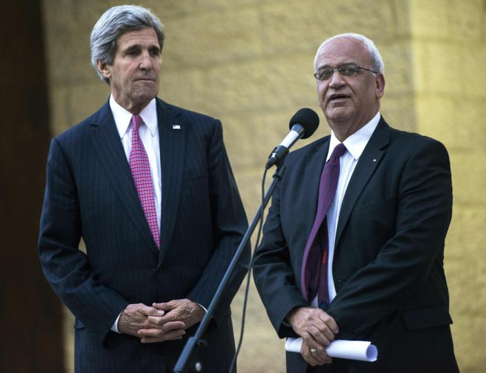 FILE - In this Jan. 4, 2014 file photo, U.S. Secretary of State John Kerry, left, listens to Palestinian negotiator Saeb Erekat make a statement to the press after meeting with Palestinian President Mahmoud Abbas at the presidential compound in the West Bank city of Ramallah. Erekat, a veteran peace negotiator and prominent international spokesman for the Palestinians for more than three decades, died Tuesday, Nov. 10, 2020. He was 65. (AP Photo/Brendan Smialowski, Pool, File)