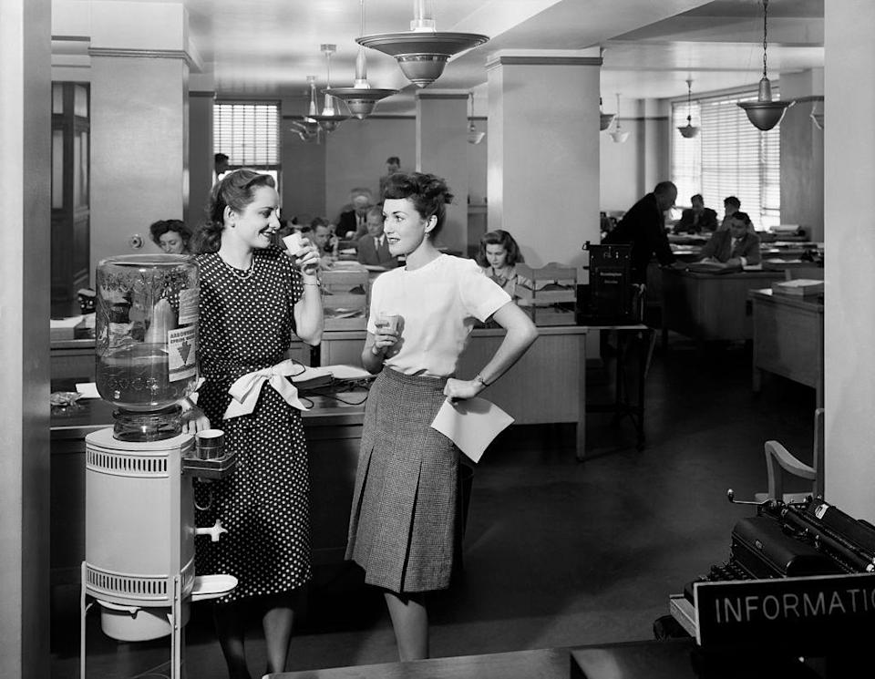 <p>Two women gather around the cooler for a quick break to chat while having a drink of water. Throwback to when water cooler convos took place around actual water coolers! </p>