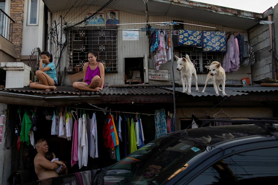 Girls hang out with their dogs on the roof of their house as the Philippine government enforces home quarantine to contain the coronavirus disease (COVID-19) outbreak in Metro Manila, Philippines. REUTERS/Eloisa Lopez