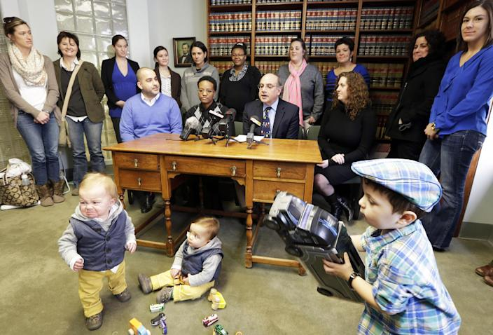 Attorney Alphonse Gerhardstein, seated second from right, answers questions Monday, Feb. 10, 2014, during a news conference in Cincinnati. Four legally married gay couples filed a federal civil rights lawsuit Monday seeking a court order to force Ohio to recognize same-sex marriages on birth certificates despite a statewide ban. (AP Photo/Al Behrman)