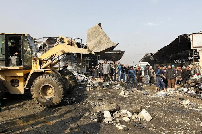 Iraqis observe as a bulldozer removes debris from the site of a suicide car bomb attack at Baghdad's main vegetable market on January 8, 2017 (AFP Photo/Sabah Arar)