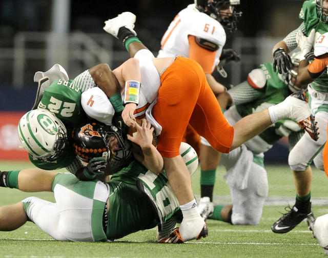 FILE - In this Dec. 21, 2013 file photo, Aledo quarterback Luke Bishop (4) is tackled by Brenham's Ryan Nunn (22) in the first half during the UIL Class 4A, Division II high school football championship game in Arlington, Texas. Nearly half of parents say they're not comfortable letting their child play football amid growing uncertainty about the long-term impact of concussions, according to an Associated Press-GfK poll. A majority, however, say they haven't prevented their child from playing the game they love. (AP Photo/Matt Strasen)