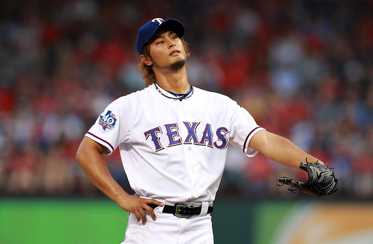 ARLINGTON, TX - APRIL 09:  Yu Darvish #11 of the Texas Rangers reacts after giving up a walk against Munenori Kawasaki #61 of the Seattle Mariners  at Rangers Ballpark in Arlington on April 9, 2012 in Arlington, Texas.  (Photo by Ronald Martinez/Getty Images)
