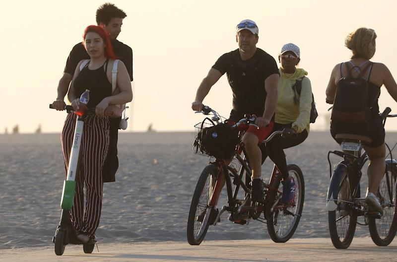 LOS ANGELES, CA - AUGUST 13: A man and woman (L) ride a shared dockless electric scooter next to bicycles along Venice Beach on August 13, 2018 in Los Angeles, California. Shared e-scooter startups Bird and Lime have rapidly expanded in the city. Some city residents complain the controversial e-scooters are dangerous for pedestrians and sometimes clog sidewalks. A Los Angeles Councilmember has proposed a ban on the scooters until regulations can be worked out. (Photo by Mario Tama/Getty Images)