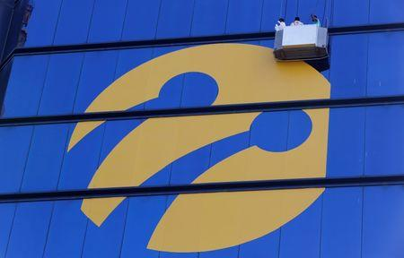 Workers install the logo of Turkcell, country's top mobile operator, on the Tat Towers in Istanbul