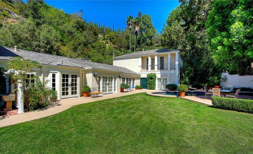 Spanning an acre, the gated property include a Traditional-style home with two wings and an oval-shaped swimming pool.