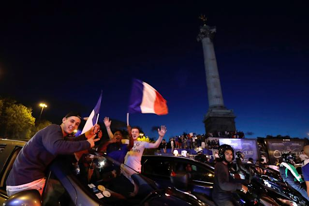 <p>Motorists and bystanders wave flags as they celebrate France's victory at Bastille in Paris on July 10, 2018, after the final whistle of the Russia 2018 World Cup semi-final football match between France and Belgium. (Photo by Thomas SAMSON / AFP) </p>