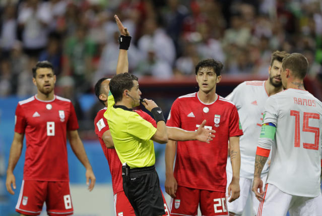 Referee Andres Cunha from Uruguay blows his whistle and indicates that VAR had shown that Iran's Morteza Pouraliganji had handled the ball into the net, and no goal was givenduring the group B match between Iran and Spain at the 2018 soccer World Cup in the Kazan Arena in Kazan, Russia, Wednesday, June 20, 2018. (AP Photo/Sergei Grits)