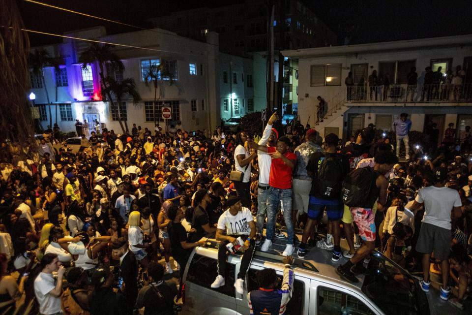 Crowds gather in the street while a speaker blasts music an hour past curfew in Miami Beach, Fla., on Sunday, March 21, 2021. An 8 p.m. curfew has been extended in Miami Beach after law enforcement worked to contain unruly crowds of spring break tourists. (Daniel A. Varela/Miami Herald via AP)
