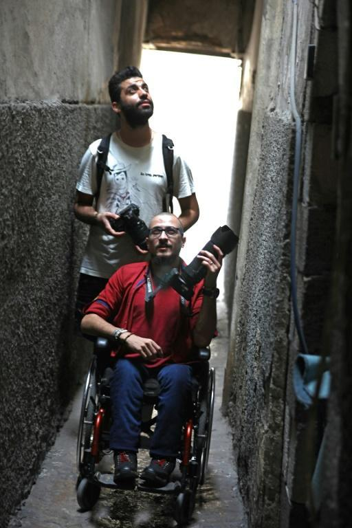 Bader al-Hajjami leads the way as he and his friend Ahmad Moussa set out to take photographs in an alley of Syria's capital Damascus