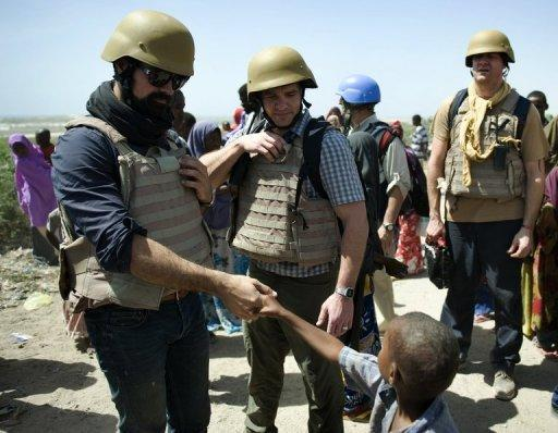 Russia's Evgeny Lebedev (L), seen here meeting a young internally-displaced person at a camp in Somalia's war-shattered capital Mogadishu on February 13. Lebedev is the son of Russian oligarch Alexander Lebedev and a British press baron