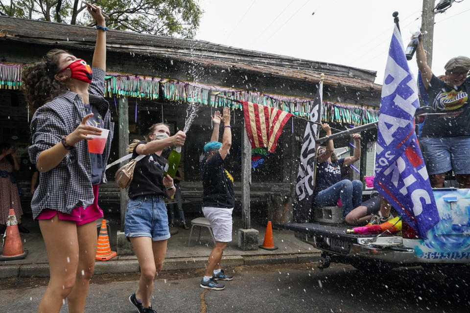 People celebrate outside Vaughn's Lounge in the Bywater section of New Orleans, Saturday, Nov. 7, 2020, after news outlets called the Presidential election in favor of President-elect Joe Biden and his running mate, Vice President-elect Kamala Harris. (AP Photo/Gerald Herbert)