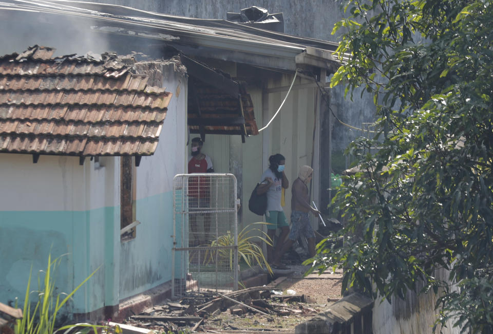 Sri Lankan inmates of the Mahara prison come out from a damaged building following an overnight unrest in Mahara, outskirts of Colombo, Sri Lanka, Monday, Nov. 30, 2020. Sri Lankan officials say six inmates were killed and 35 others were injured when guards opened fire to control a riot at a prison on the outskirts of the capital. Two guards were critically injured. Pandemic-related unrest has been growing in Sri Lanka's overcrowded prisons. (AP Photo/Eranga Jayawardena)