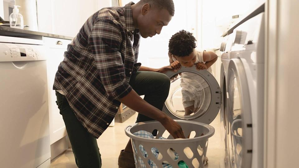 African American father and son washing clothes in washing machine at home.
