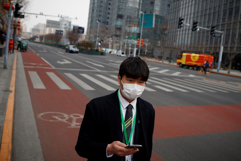 A businessman wears a face mask in the Central Business District in Beijing. Source: Reuters/Thomas Peter
