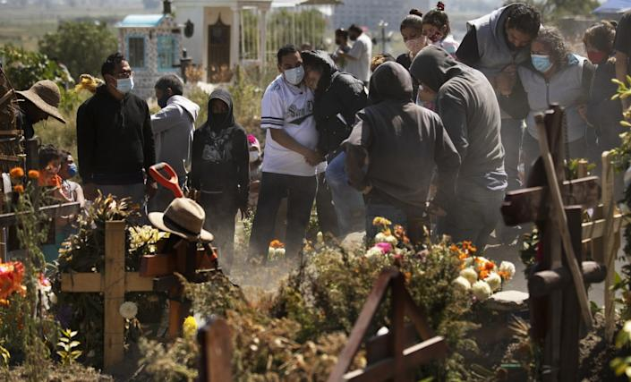 A group of people stand around a gravesite