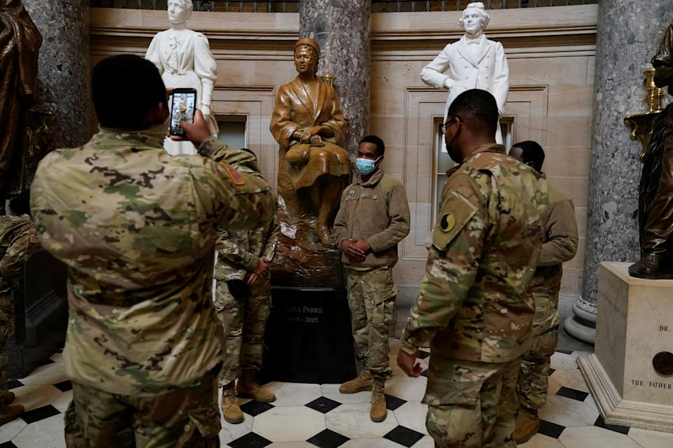 National Guard member poses for a picture with a statue of the civil rights activist Rosa Parks