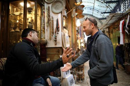 Eitan Klein, deputy director of the Israel Antiquities Authority's robbery prevention unit, greets a man near shops selling antiques at a market in Jerusalem's Old City November 25, 2018. Picture taken November 25, 2018. REUTERS/Corinna Kern