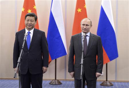 """Russia's President Vladimir Putin (R) and his Chinese counterpart Xi Jinping take part in a video link with the officership of the nuclear-powered missile cruiser """"Pyotr Veliky"""" and the Chinese missile frigate """"Yancheng"""" at the Bocharov Ruchei state residence in Sochi, February 6, 2014. REUTERS/Alexei Nikolsky/RIA Novosti/Kremlin"""