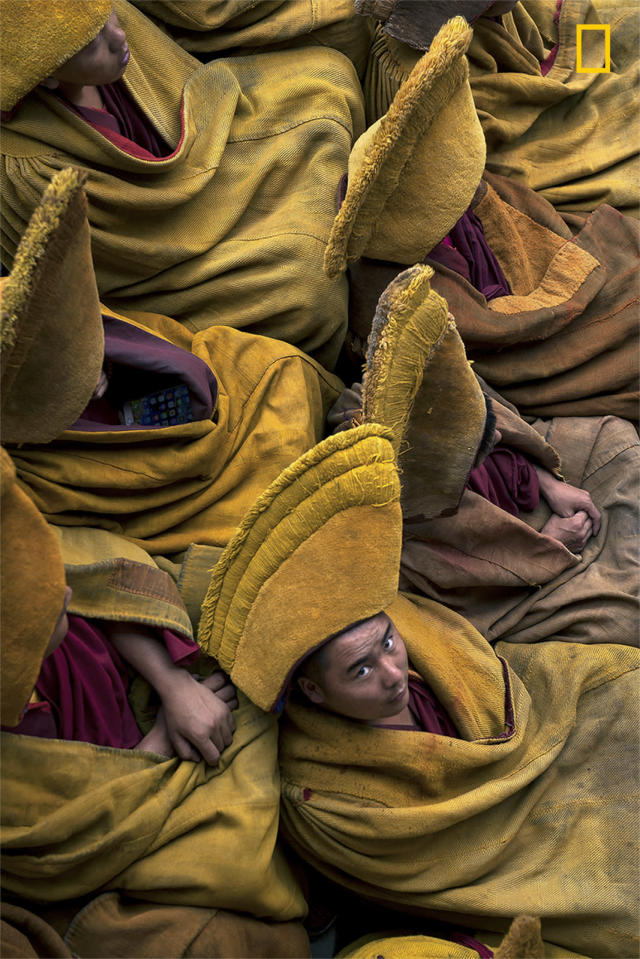 <p>Tibetan monks during the weekly pray in Tashi LhunPo Monastery in Tibet. The Tashi LhunPo Monastery, founded in 1447 by the 1st Dalai Lama, is historically important and the most influential monastery in Shigatse, the second-largest city in Tibet. Currently, 2000 monks reside there. (© Mattia Passarini/National Geographic Travel Photographer of the Year Contest) </p>