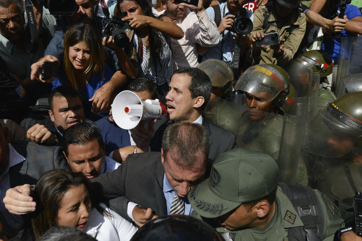 Opposition leader Juan Guaido yells into a megaphone for National Guards to let him and all opposition lawmakers into the National Assembly, outside the legislature in Caracas, Venezuela, Tuesday, Jan. 7, 2020. Guaidó and lawmakers who back him pushed their way into the legislative building on Tuesday following an attempt by rival legislators to take control of the congress, and declared Guaidó the president of the only opposition-controlled institution. (AP Photo/Matias Delacroix)
