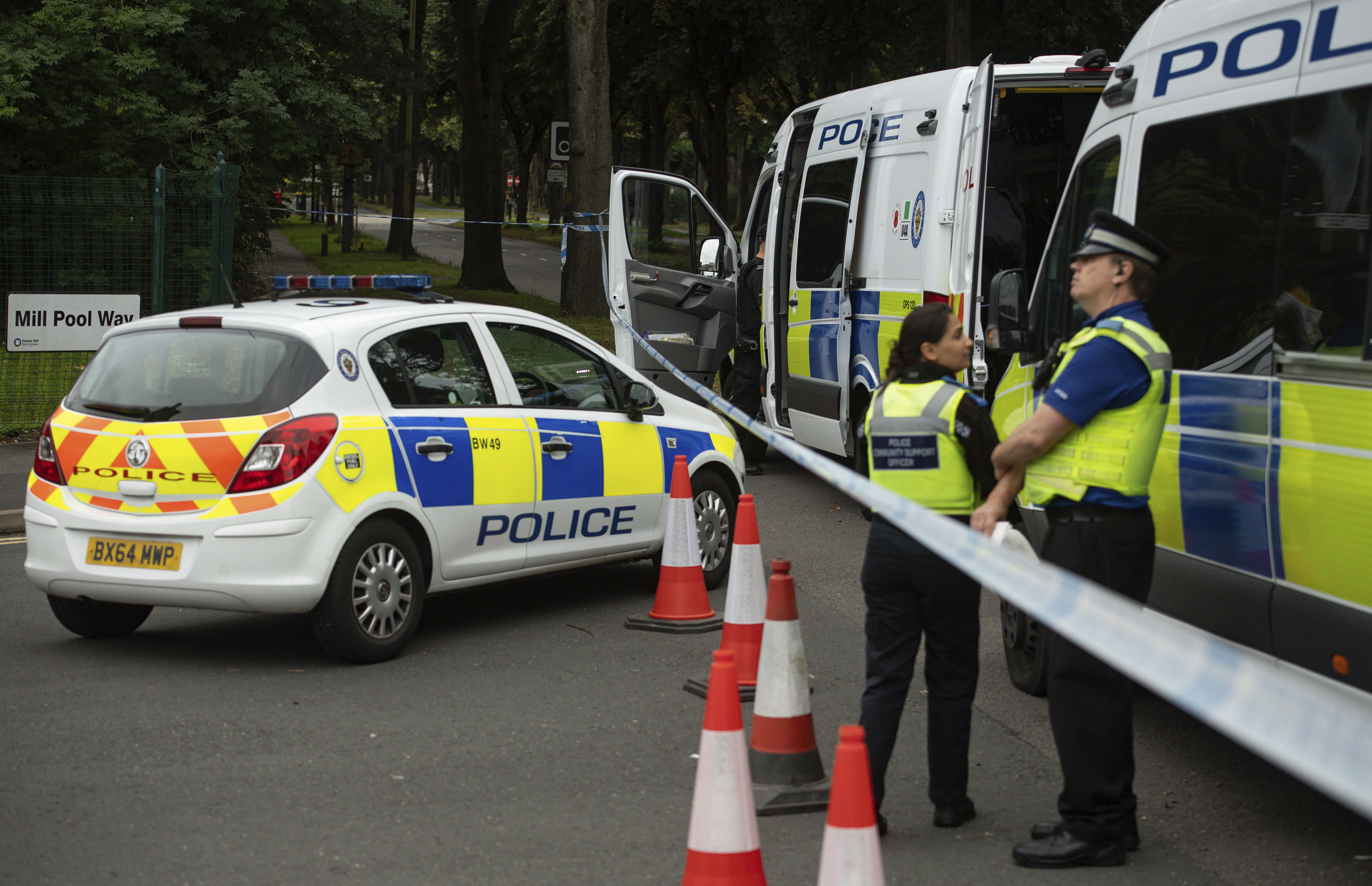 Police officers secure the area after a man was found fatally stabbed late Saturday, in Birmingham, England, Sunday Aug. 23, 2020. A 15-year-old girl and a 28-year-old woman were detained at the scene and according to the police, they remain in custody. (Jacob King/PA via AP)