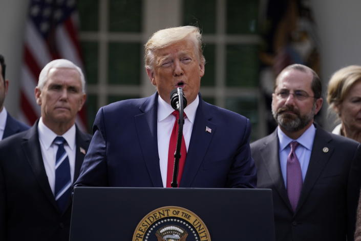 President Donald Trump speaks during a news conference about the coronavirus in the Rose Garden of the White House, Friday, March 13, 2020, in Washington. Department of Health and Human Services Secretary Alex Azar, right, and Vice President Mike Pence listen. (AP Photo/Evan Vucci)