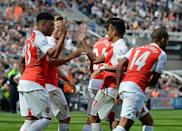 Arsenal's Alex Oxlade-Chamberlain is congratulated by teammates after his shot deflects off Newcastle United's Fabricio Coloccini for Arsenal's opening goal, during their English Premier League match, in Newcastle-upon-Tyne, on August 29, 2015 (AFP Photo/Oli Scarff)