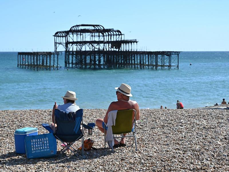 People sunbathe on the beach near the derelict West Pier in Brighton on the south coast of England on May 31, 2020 on the eve of a further relaxation of the novel coronavirus lockdown rules: AFP via Getty Images