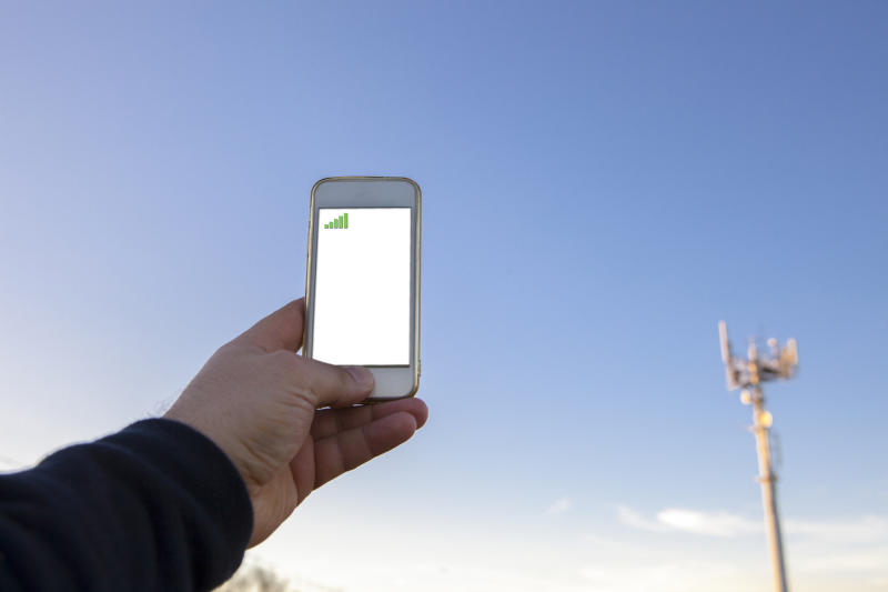 A man holds a smartphone up next to a cellular tower.