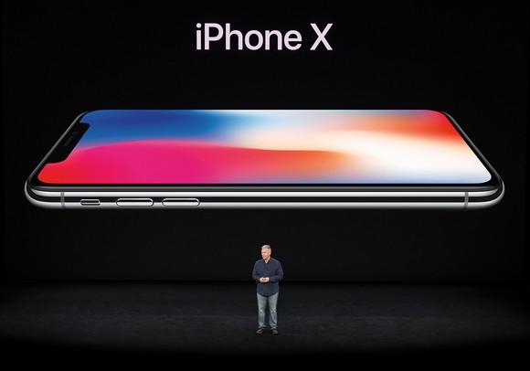 Apple marketing chief Phil Schiller standing on stage with an image of the iPhone X projected behind him.