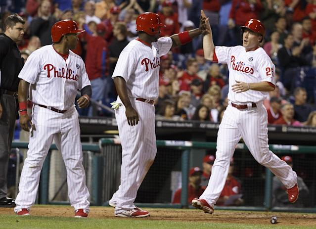 Philadelphia Phillies' Ryan Howard, center, gives Cody Asche, right, a high five with Marlon Byrd, left, score on the double by Domonic Brown during the seventh inning of a baseball game against the Cincinnati Reds, Saturday, May 17, 2014, in Philadelphia. The Phillies win 12-1. (AP Photo/Chris Szagola)