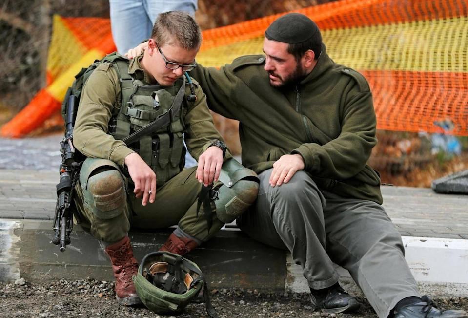 An Isreali soldier is consoled at the site of a Palestinian drive-by shooting attack outside the West Bank settlement of Givat Asaf, northeast of Ramallah ( AHMAD GHARABLI/AFP/Getty Images))