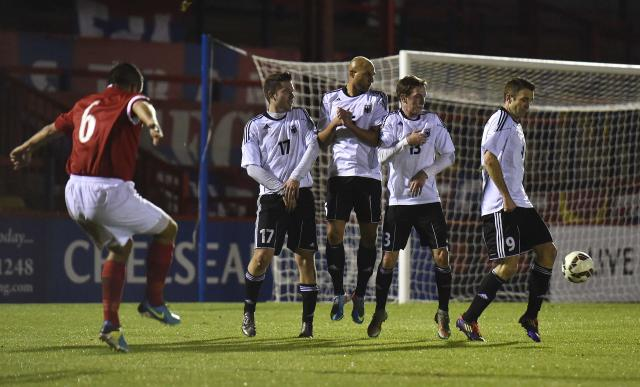 British army player Martin Molyneux (L) takes a free-kick during a soccer match between the British Army and German Bundeswehr at Aldershot Town FC stadium in Aldershot in south England, December 17, 2014. The two teams were playing each other in a 'Game of Truce' soccer match, commemorating 100 years since the famous peaceful interlude to fighting in World War I when members of the opposing British and German forces played a game of soccer in No Man's Land on Christmas Day 1914. REUTERS/Toby Melville (BRITAIN - Tags: SPORT SOCCER POLITICS ANNIVERSARY CONFLICT MILITARY)