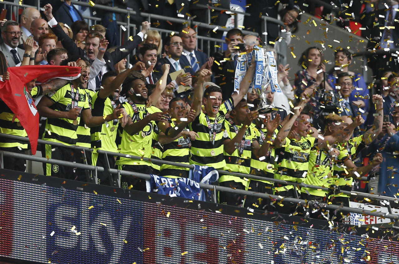 "Britain Football Soccer - Reading v Huddersfield Town - Sky Bet Championship Play-Off Final - Wembley Stadium, London, England - 29/5/17 Huddersfield Town celebrate with the trophy after winning the Sky Bet Championship Play-Off Final and getting promoted to the Premier League  Action Images via Reuters / Matthew Childs Livepic EDITORIAL USE ONLY. No use with unauthorized audio, video, data, fixture lists, club/league logos or ""live"" services. Online in-match use limited to 45 images, no video emulation. No use in betting, games or single club/league/player publications.  Please contact your account representative for further details."