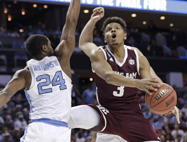Texas A&M's Admon Gilder (3) drives against North Carolina's Kenny Williams (24) during the first half of a second-round game in the NCAA men's college basketball tournament in Charlotte, N.C., Sunday, March 18, 2018. (AP Photo/Gerry Broome)
