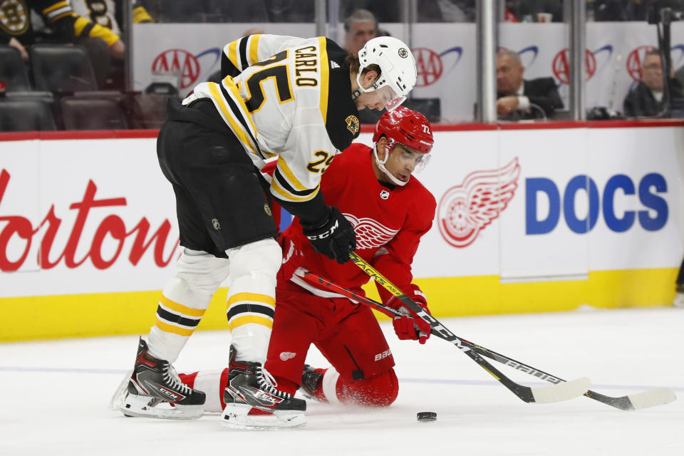Boston Bruins defenseman Brandon Carlo (25) and Detroit Red Wings left wing Andreas Athanasiou (72) battle for the puck in the second period of an NHL hockey game Sunday, Feb. 9, 2020, in Detroit. (AP Photo/Paul Sancya)