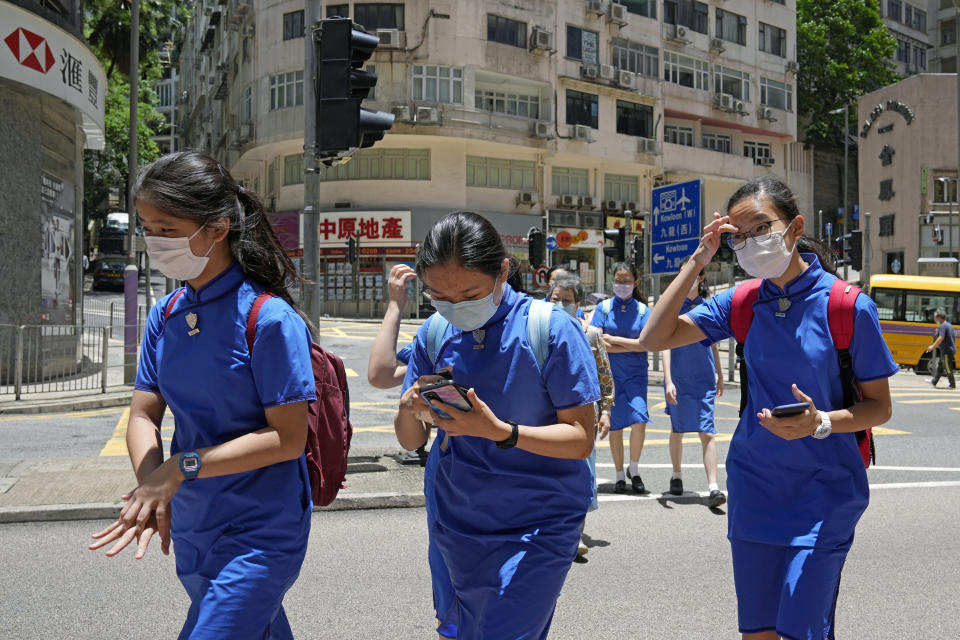 Students wearing face masks to prevent the spread of coronavirus, walk across a street in Hong Kong, Thursday, June 10, 2021. Government officials said Thursday that they will expand the vaccination drive to about 240,000 children from 12 to 15 years old starting Friday, joining other countries such as Singapore and the U.S. that have started vaccinating children. (AP Photo/Kin Cheung)