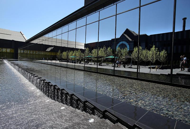 In this Aug. 5, 2013 photo, water flows near a reflecting pool outside the new 145,000-square-foot University of Oregon Football Performance Center on the University of Oregon campus Eugene, Ore. The glass facade reflects the Casanova Center, which houses non-football athletic operations. (AP Photo/Brian Davies)