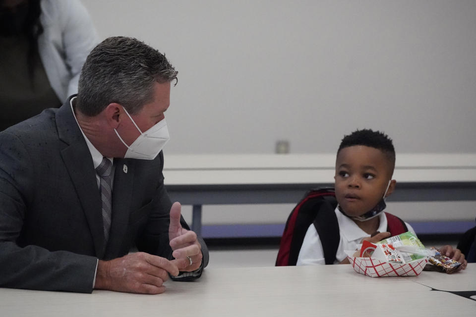 Mike Burke, left, Palm Beach County Superintendent of Schools, chats with Jaden Williams, 5, as Williams eats breakfast, Tuesday, Aug. 10, 2021, during the first day of school at Washington Elementary School in Riviera Beach, Fla. (AP Photo/Wilfredo Lee)