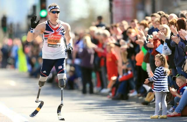 Great Britain's paralympic gold medallist Richard Whitehead waves to crowds during the 2013 London Marathon. Whitehead set a new world record when winning gold in the 200m in the T42 category at London 2012 the previous year (Mike Egerton/PA)