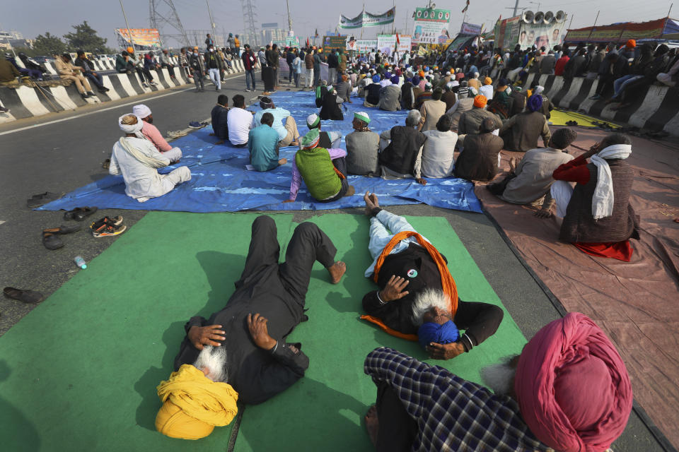 Indian farmers listen to a speaker as they block a highway in protest against new agricultural laws in New Delhi, India, on Dec. 21, 2020. India's prime minister Narendra Modi Friday held virtual talks with farmers from six states and asked them to explain how the government's agricultural policies have benefited them, a month after facing massive farmer protests that have rattled his administration. (AP Photo/Manish Swarup)