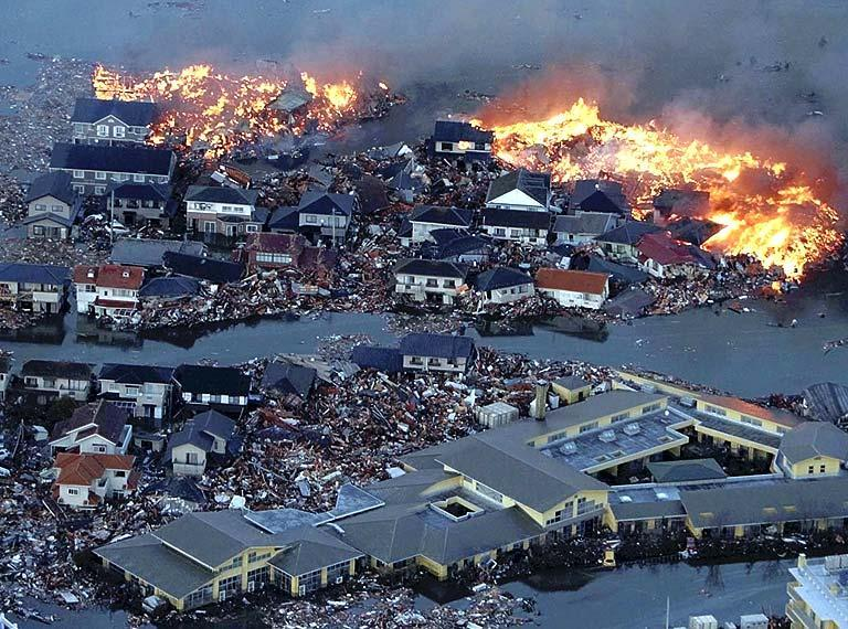 Houses are in flame while the Natori river is flooded over the surrounding area by tsunami tidal waves in Natori city, Miyagi Prefecture, northern Japan, March 11, 2011, after strong earthquakes hit the area. (AP Photo/Yasushi Kanno